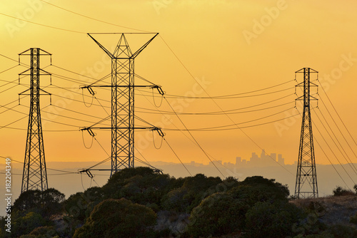 Los Angeles skyline at sunset viewed from a distance through power lines Poster