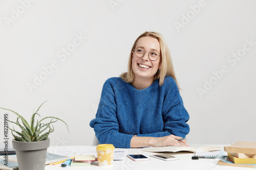 Happy female student busy with presentation for seminar, reads book