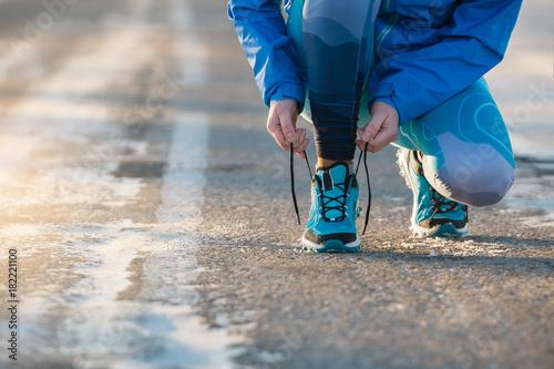 Kobieta biegacz wiąże shoelaces. Zdrowy tryb życia.