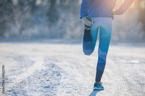 Staande foto Jogging Runner stretching in winter Park. A healthy way of life.