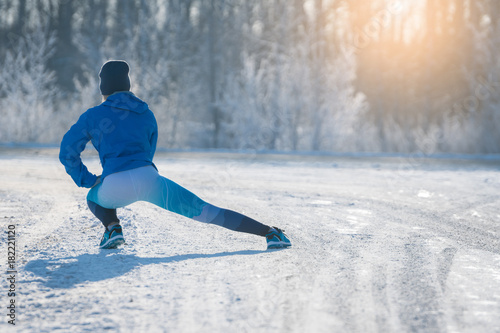 Fototapeta Runner stretching in winter Park. A healthy way of life.