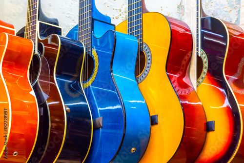 colorful-wooden-guitars-hanging-on-wall-of-store-showroom