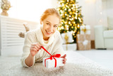 happy woman with gift at morning near Christmas tree - 182230594