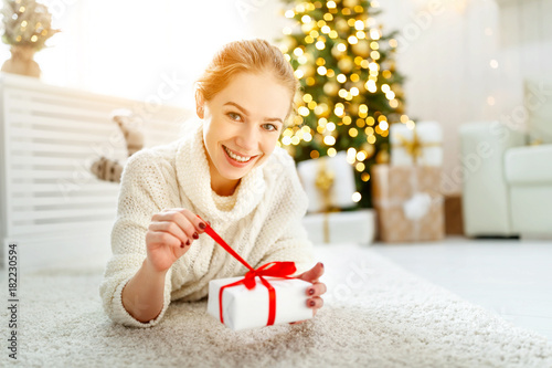 happy woman with gift at morning near Christmas tree