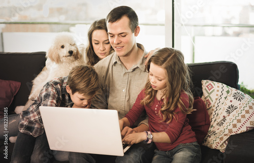 Young happy family watching movie on laptop together at home