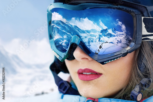 obraz lub plakat Portrait of young woman at the ski resort on the background of mountains and blue sky.A mountain range reflected in the ski mask