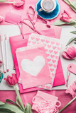 Lovely pink mock up with tulips, paper package with hearts, marker pen, tags and cup of coffee on creative desktop, top view, frame. Layout of greeting card for Mothers , Valentines day or birthday - 182237553