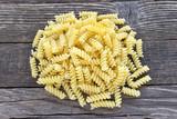 Fusilli pasta on wooden background - 182246104