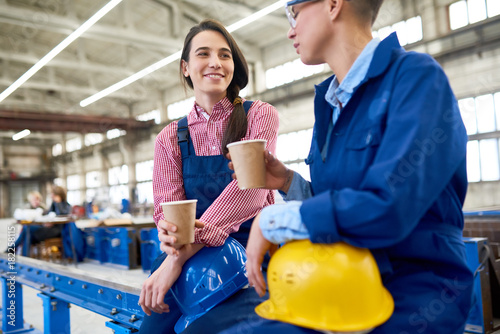 Positive young female construction workers drinking coffee from disposable cups and talking while resting during break