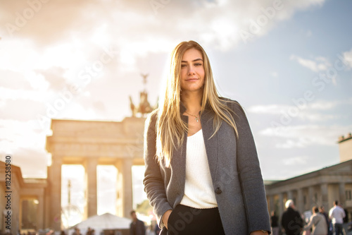 Portrait of smiling fashionable young woman in front of Brandenburger Tor in Berlin, Germany. © Bojan