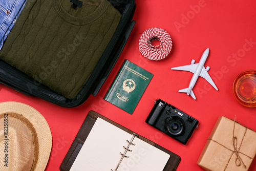 Preparation for travel concept - passport, camera, cup of tea, notepad on red background Poster
