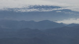 aerial shot from plane flying above the mountains in daytime