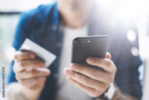 Hands with smartphone and credit card