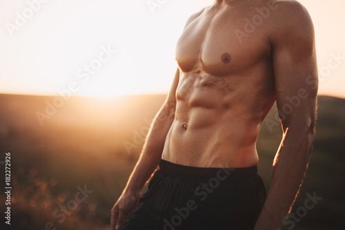 Wall mural Crop muscular man in sunset