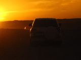 silhouettes of cars in the desert in the rays of the setting sun - 182280757