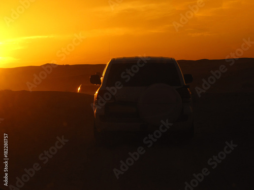 Staande foto Dubai silhouettes of cars in the desert in the rays of the setting sun