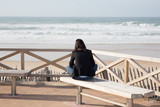 back view of young woman enjoy sun on bench beach