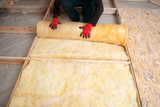 Work composed of mineral wool insulation in the floor, floor heating insulation , warm house, eco-friendly insulation, a builder at work - 182285381