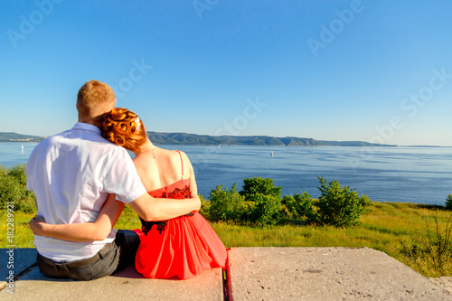 young loving couple people are looking at the sea and mountains Poster