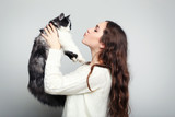 Beautiful young woman holding cat on grey background - 182292707