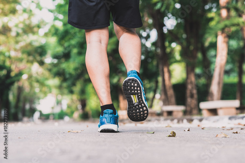 Tuinposter Jogging Back view of runner feet jogging in morning at park