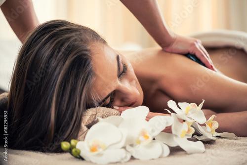 Frau bei hot stone Massage und Wellness