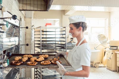 Bäcker Frau holt Brot und Brötchen aus Backofen