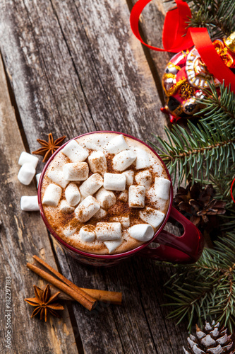 Foto op Canvas Chocolade hot chocolate on wooden background with fir tree and snow effect. Traditional beverage for winter time