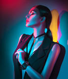 Portrait of sexy young woman in black clothes,  fashion accessories, bright makeup in neon light