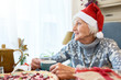 Portrait of smiling senior woman wearing Santa hat looking to window pensively enjoying  Christmas dinnerat home  sitting at table and drinking tea, copy space