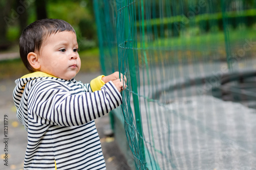 Little sad latin boy trying to break a metal fence.