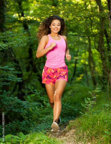 Tuinposter Jogging active young fit woman runs in green forest on late summer afternoon