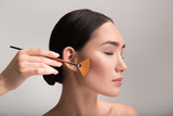 Close-up profile of face of pensive asian naked girl is attending beauty salon while visagiste is applying blusher on her check with professional brush. Lady is standing with closed eyes. Isolated - 182317507