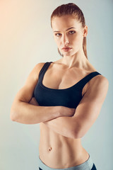 Stop killing time. Beautiful sportswoman wearing a navy blue sport clothing posing with her arms crossed and looking into the camera confidently.