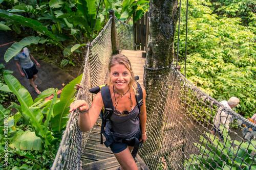 Caraïbes, Martinique, jardin de balata : femme qui traverse un pont suspendu