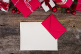Christmas gift giving and list to Santa Claus concept - christmas presents in red paper boxes on wooden table, flat lay with copy space on empty paper note