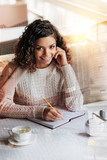 Creative. Cute positive young author sitting at the table in a beautiful cafe and smiling cheerfully while working at her first book - 182322142