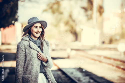 Young woman with hat on train station Poster