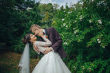 Beautiful couple of happy stylish newlyweds on a walk in the sunny summer park or garden on their wedding day - 182323140