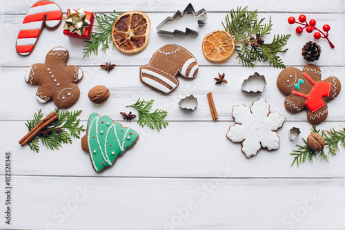 Fototapeta Homemade delicious Christmas gingerbread cookies on the white wooden background.