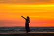 Feeling positive, winning, success, achieving life goals, life is good, positive mood.  Silhouette beautiful smiling woman thumb up on the sunset/Girl enjoys the beautiful sunset / Meet a new day
