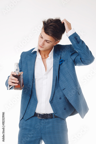 Plakat Isolated portrait of handsome elegant young man in suit with a bottle of whiskey