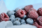 Fresh raspberries and blueberries are frozen on cold blue ice