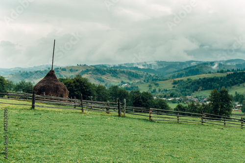 Foto op Canvas Olijf mountain landscape with a small cozy village on the flat land, a place in the autumn fog