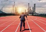 business man running to oil refinery plant - 182336306