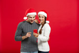 Christmas Concept - Young handsome and beautiful couple enjoy checking on mobile phone in christmas day. - 182349945
