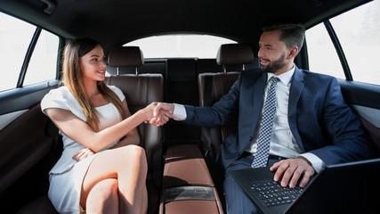 Beautiful couple using laptop computer in car