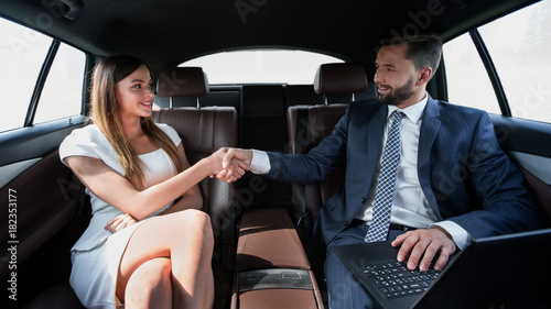 Beautiful couple using laptop computer in car - 182353177