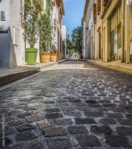 Fototapeta Low angle image of narrow, cobblestone street in Europe