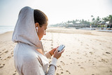 Young woman is listening to the music on the phone before jogging on the beach at the sunrise - 182368559